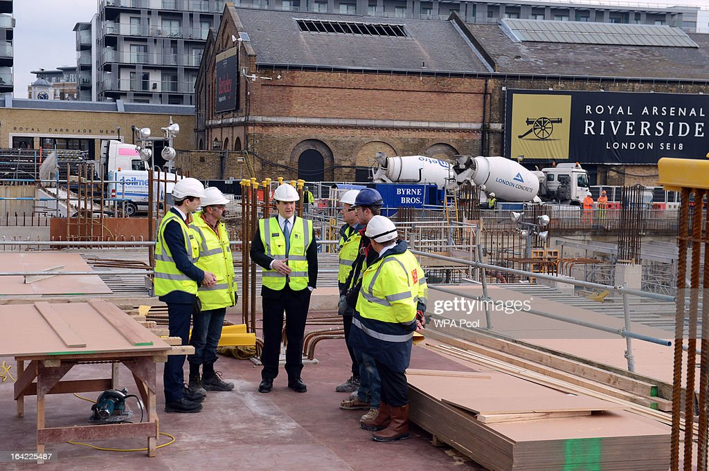 Chancellor George Osborne (C) speaks to construction workers at the Berkeley Homes Royal Arsenal Riverside development in Woolwich on March 21, 2013 in south east London, England. The Chancellor of the Exchequer visited homebuyers and construction workers at the housing development site the day after he announced in his Budget speech the government's measures for assisting first-time buyers and existing home-owners in moving up the property ladder, with a GBP £3.5 billion investment in government loans to financially stretched home-buyers and GBP £12 billion towards a scheme to increase availability of mortgages to first-time buyers unable to afford a large deposit. Homebuyers will be able to borrow up to 20% per cent of the value of most new-build properties interest-free for five years.