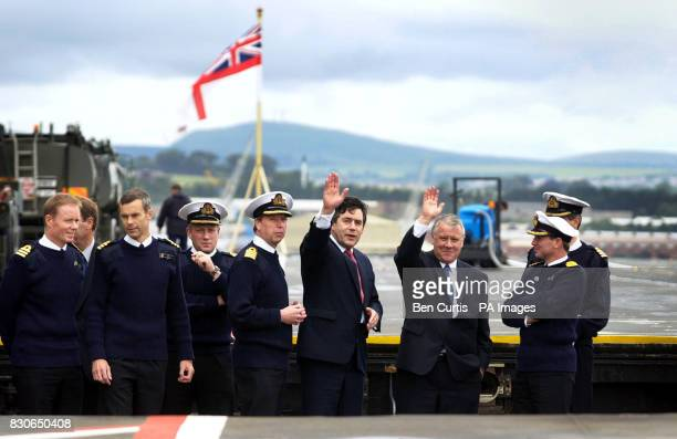 Chancellor Gordon Brown and Armed Forces Minister Adam Ingram wave as they leave the HMS Ark Royal as it sits at anchor next to the Forth Road and...