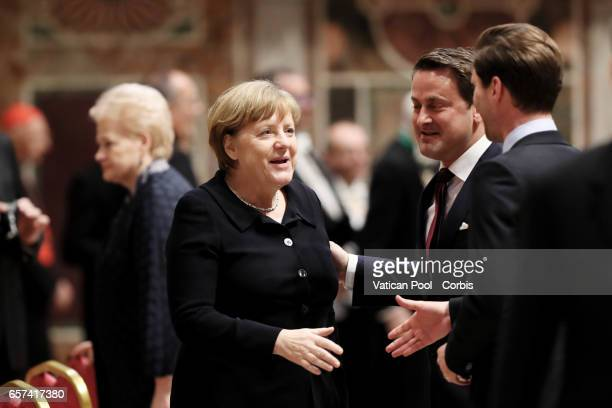 Chancellor of Germany Angela Merkel greets Luxembourg's Prime Minister Xavier Bettel and partner Gauthier Destenay during a meeting between Pope...
