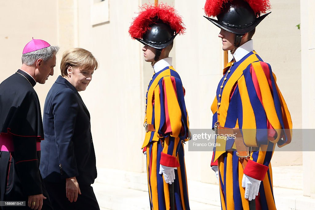 Chancellor of Germany Angela Merkel is received by Prefect of the Pontifical House and former personal secretary of Pope Benedict XVI Georg Ganswein as she arrives at the Cortile di San Damaso for a visit with Pope Francis on May 18, 2013 in Vatican City, Vatican.