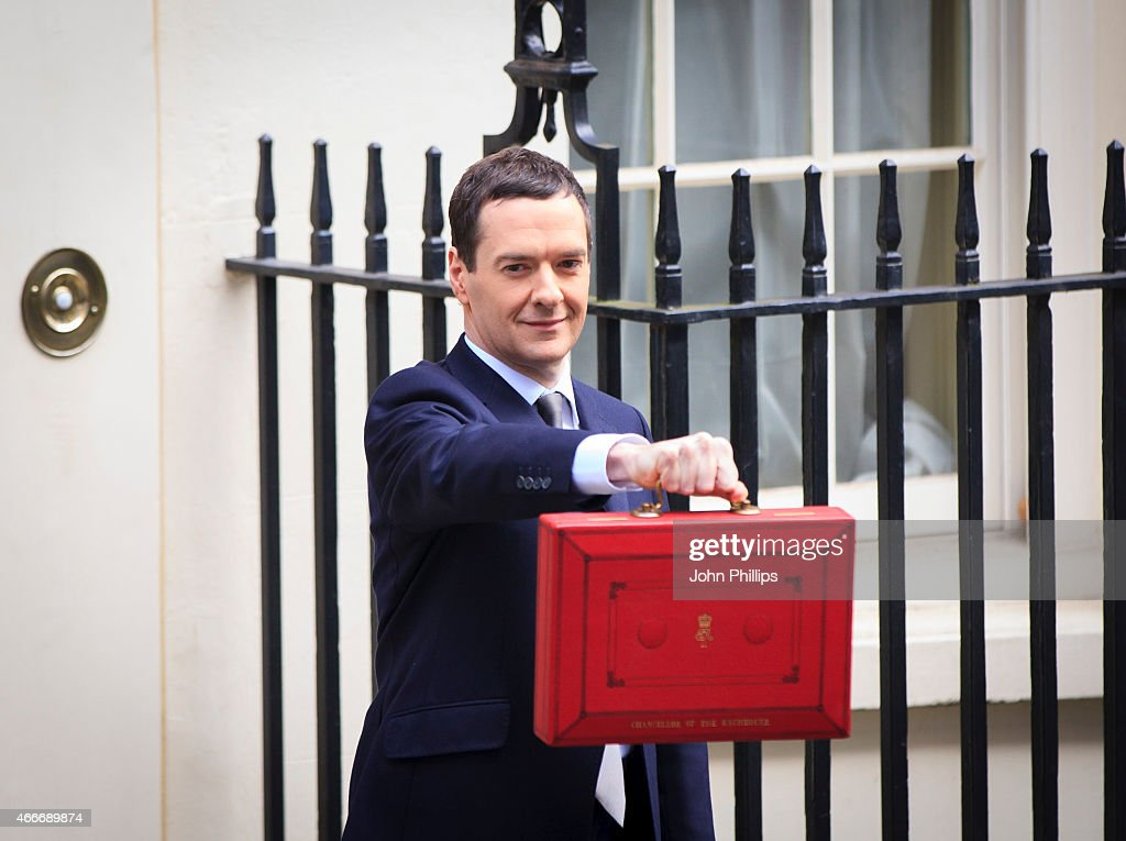 Chancellor of the Exchequer <a gi-track='captionPersonalityLinkClicked' href=/galleries/search?phrase=George+Osborne&family=editorial&specificpeople=5544226 ng-click='$event.stopPropagation()'>George Osborne</a> holds his ministerial red box up to the media as he leaves number 11 Downing Street for Parliament on March 18, 2015 in London, England. The Chancellor is presenting his 5th Budget to Members of Parliament today, the last before the General Election on May 7, 2015. at 11 Downing Street on March 18, 2015 in London, England.