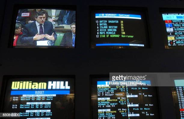 Chancellor of the Exchequer Gordon Brown is pictured during his budget speech on a television screen in a York betting shop while standing above a...