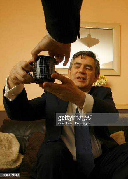 Chancellor of the Exchequer Gordon Brown takes a cup of tea from Sally Hatcher a tenant of an ecofriendly community housing development during a...