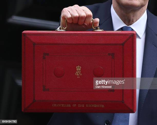 Chancellor of the Exchequer Philip Hammond holds the budget box up to the media as he leaves 11 Downing Street on March 8 2017 in London England...