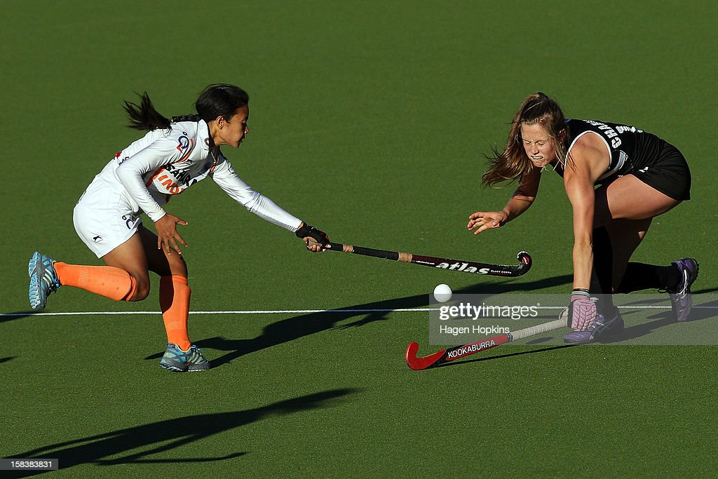 Chanchan Devi Thokchom of India and Sam Charlton of New Zealand compete for the ball during the match between New Zealand and India at the National Hockey Stadium on December 15, 2012 in Wellington, New Zealand.
