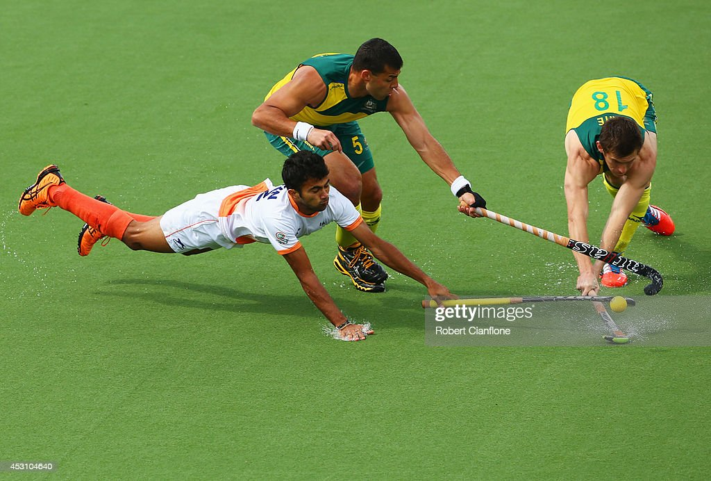 Chandanda Nikkin Thimmaiah of India (L) battles with Chris Ciriello (C) and Tristan White (R) of Australia in the gold medal match between India and Australia at Glasgow National Hockey Centre during day eleven of the Glasgow 2014 Commonwealth Games on August 3, 2014 in Glasgow, United Kingdom.