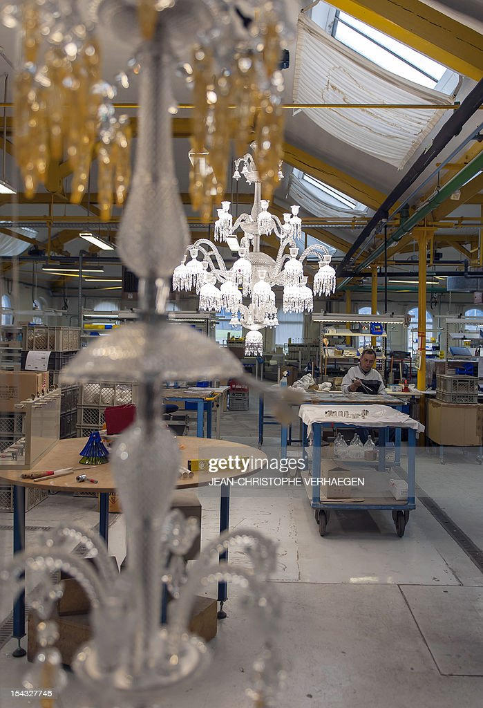Chandeliers being assembled are displayed on October 16, 2012 at the crystalworks of French crystal glass maker Baccarat in Nancy, eastern France. AFP PHOTO / JEAN-CHRISTOPHE VERHAEGEN