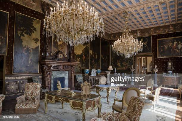 Chandeliers hang over armchairs and tables as 19th century portraits in ornate frames adorn the walls of a sitting room inside the Villa Les Cedres a...