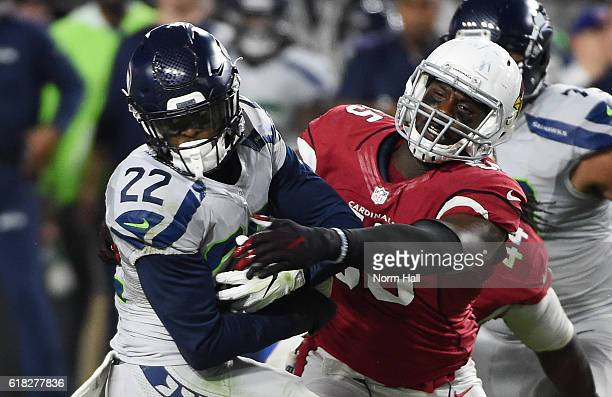 Chandler Jones of the Arizona Cardinals attempts to strip the ball away from CJ Prosise of the Seattle Seahawks at University of Phoenix Stadium on...