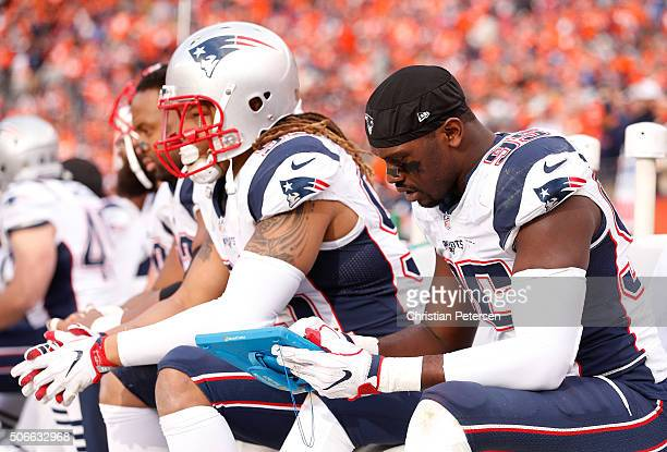 Chandler Jones of the New England Patriots holds a Microsoft Surface tablet on the sideline in the third quarter against the Denver Broncos in the...