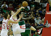 Chandler Parsons and Omer Asik of the Houston Rockets battle for a rebound with Kevin Garnett of the Boston Celtics at the Toyota Center on December...