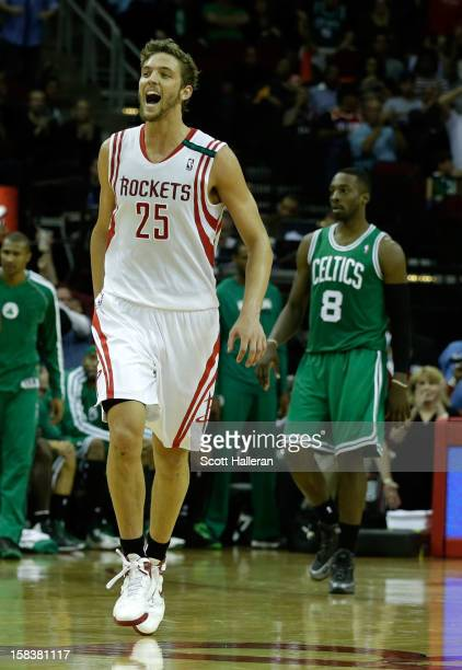 Chandler Parsons of the Houston Rockets celebrates after a play as Jeff Green of the Boston Celtics walks to the bench at the Toyota Center on...