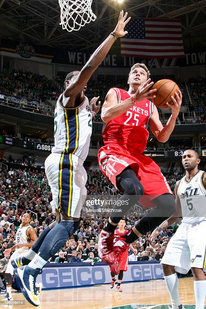Chandler Parsons #25 of the Houston Rockets goes to the basket against Al Jefferson #25 at Energy Solutions Arena on November 19, 2012 in Salt Lake City, Utah.