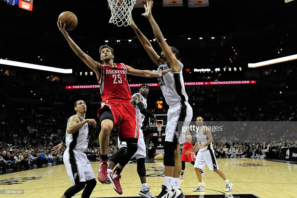 Chandler Parsons #25 of the Houston Rockets scores against Tim Duncan #21 of the San Antonio Spurs at AT&T Center on December 28, 2012 in San Antonio, Texas. San Antonio won the game 122-116.