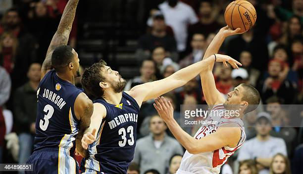 Chandler Parsons of the Houston Rockets takes a shot against Marc Gasol and James Johnson of the Memphis Grizzlies during the game at the Toyota...