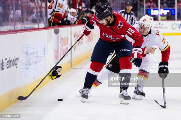 Chandler Stephenson of the Washington Capitals and Freddie Hamilton of the Calgary Flames battle for the puck in the third period at Capital One...