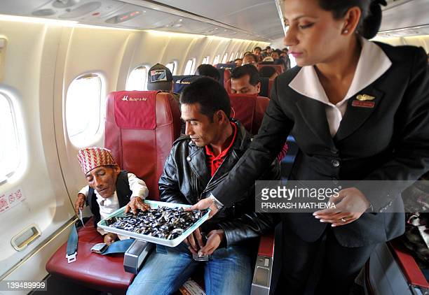 Chandra Bahadur Dangi a 72yearold Nepali who claims to be the world's shortest man at 56 centimetres in height is offered refreshments by a Buddha...