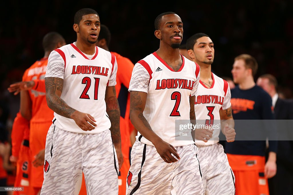 Chane Behanan #21, Russ Smith #2 and Peyton Siva #3 of the Louisville Cardinals walk back to the bench in the second half against the Syracuse Orange during the final of the Big East Men's Basketball Tournament at Madison Square Garden on March 16, 2013 in New York City.