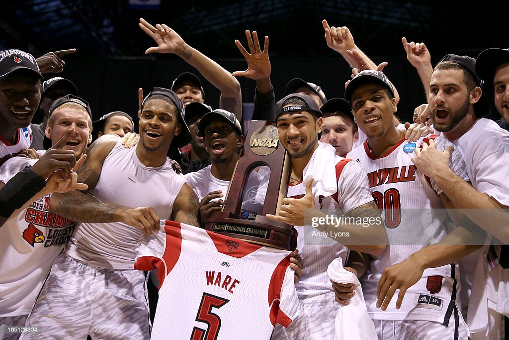 Chane Behanan #21 (holding #5 jersey of injured teammate Kevin Ware), Russ Smith #2, Peyton Siva #3, Wayne Blackshear #20 and Luke Hancock #11 of the Louisville Cardinals celebrate with the Midwest regional champion trophy after they won 85-63 against the Duke Blue Devils during the Midwest Regional Final round of the 2013 NCAA Men's Basketball Tournament at Lucas Oil Stadium on March 31, 2013 in Indianapolis, Indiana. Kevin Ware suffered a compound fracture of his leg in the first half.