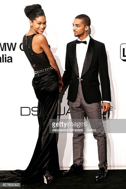Chanel Iman and guest on the AmfAR Milano 2009 red carpet during the inaugural Milan Fashion Week event at La Permanente