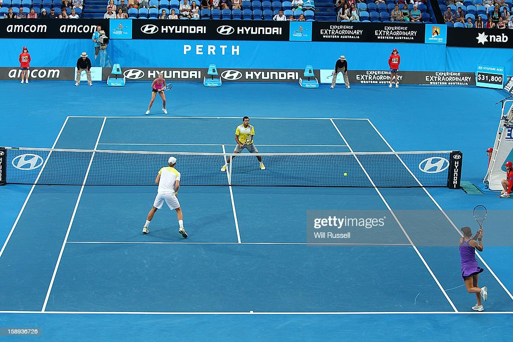 Chanelle Scheepers of South Africa plays a backhand as Kevin Anderson looks on during their mixed doubles game against Jo-Wilfried Tsonga and Mathilde Johansson of France during day seven of the Hopman Cup at Perth Arena on January 4, 2013 in Perth, Australia.