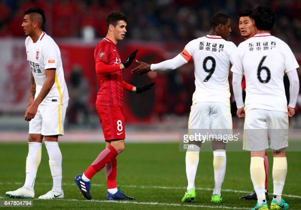 Changchun Yatai's Nigerian striker Odion Ighalo talks to Shanghai SIPG's Brazilian midfielder Oscar during their Chinese Super League match in...
