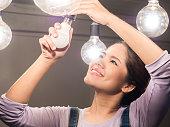 asian woman changing light bulb