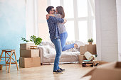 Profile view of loving young couple expressing their feeling while standing at living room of new apartment, interior design items and moving boxes on background