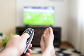 Closeup of a male hand holding remote control with his feet crossed in front of a large television set sitting in his living room and watching football