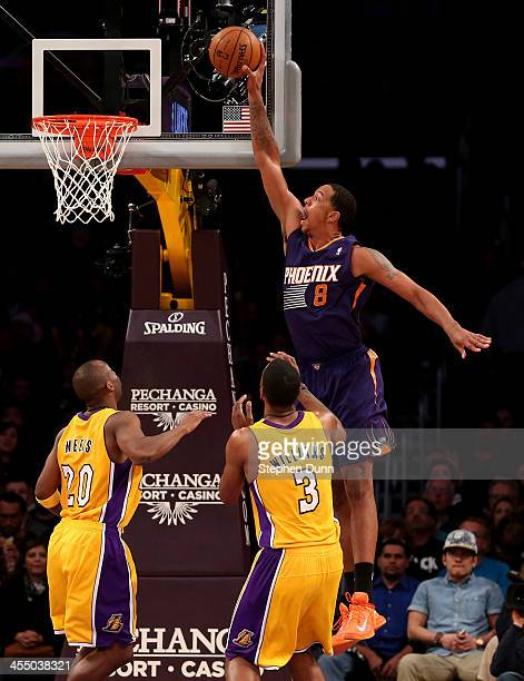 Channing Frye of the Phoenix Suns dunks over Shawne Williams and Jodie Meeks of the Los Angeles Lakers at Staples Center on December 10 2013 in Los...