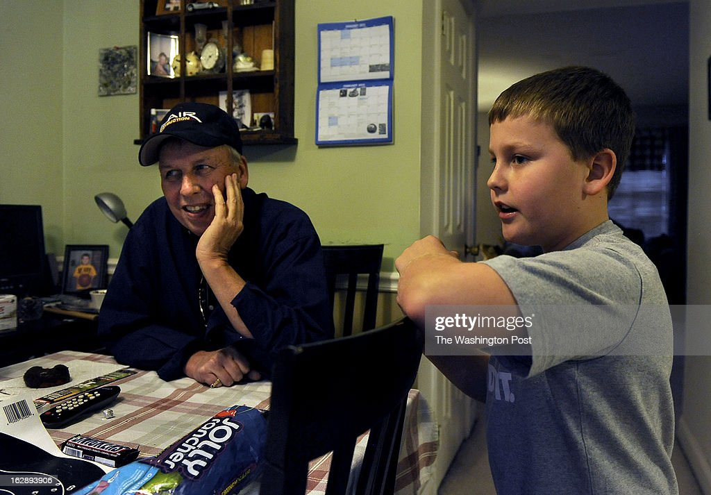 Chanse Mullinix and his grandfather (L) Greg Mullinix chat with Chanses' dad (off camera) about what pizza toppings to order as they were having take-out for dinner this night. Guns are a long time part of the family culture with the Mullinix family. Scott Mullinix and his 9 year-old son Chanse have bonded with their mutual interest in guns, hunting and sports. Photo by Michael S. Williamson/The Washington Post via Getty Images