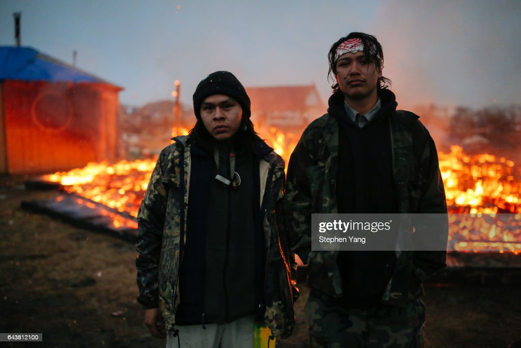 Chanse Zavalla, 22, left, and O'Shea Spencer, 20, right, stand in front of the remains of a hogan structure. Campers set structures on fire in preparation of the Army Corp's 2pm deadline to leave the Oceti Sakowin protest camp on February 22, 2017 in Cannon Ball, North Dakota. Activists and protesters have occupied the Standing Rock Sioux reservation for months in opposition to the completion of the Dakota Access Pipeline.