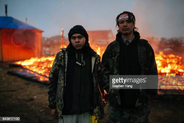 Chanse Zavalla left and O'Shea Spencer right stand in front of the remains of a hogan structure Campers set structures on fire in preparation of the...