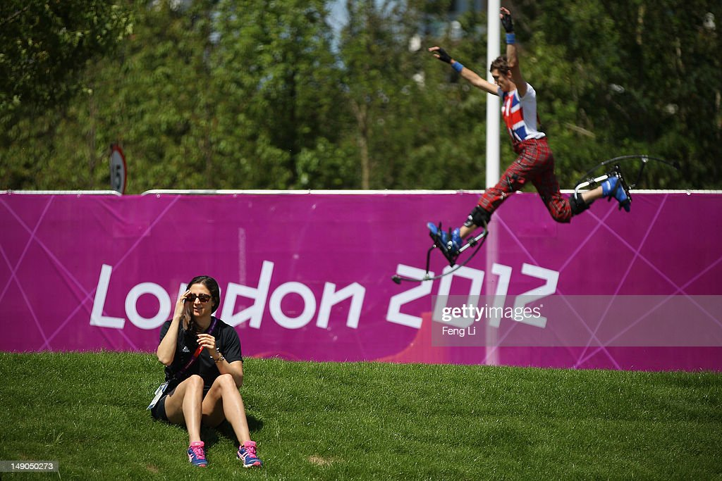 Chantal Brunner of New Zealand Olympic Delegation sits on the grass as a member of the National Youth Theatre of Great Britain practices before a welcome ceremony for the India Olympic team and delegates at Olympic Village on July 22, 2012 in London, England.