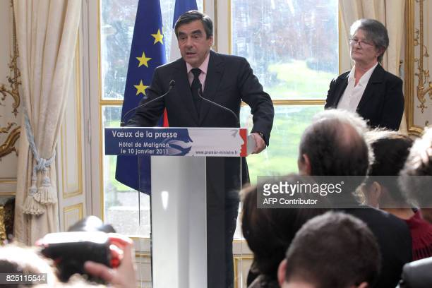 Chantal Didier President of the association of Ministries Press listens to France's Prime Minister Francois Fillon as he addresses the New Year...