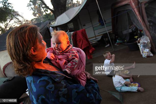 Chantell Lubbe holds her daughter Nikita as her other children eat a free meal outside their camper in a White South African squatter camp on June 7...