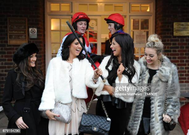 Chantelle Houghton Lucy Mecklenburgh and Kelsey Hardwick play with a jockey's whip during day 1 of the Tingle Creek Christmas Festival at Sandown...