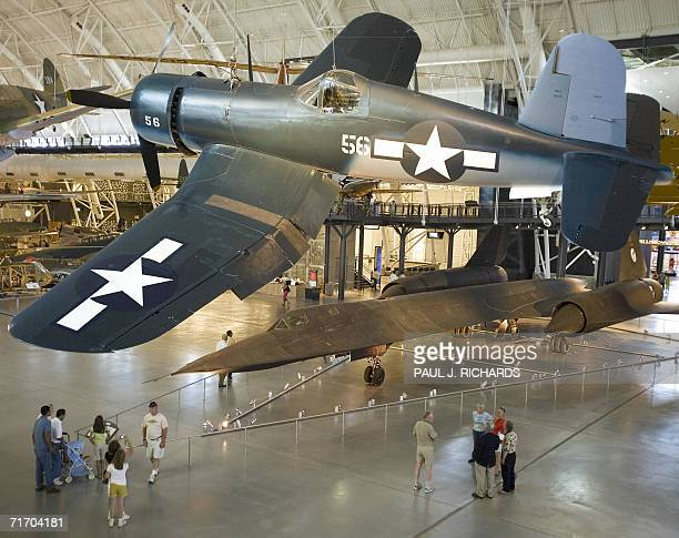 A WWII Vought F4U1D Corsair is suspended over the Lockheed SR71A Blackbird as tourists look at part of the Smithsonian Institute's UdvarHazy Air...