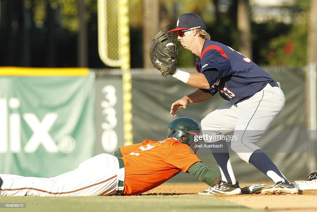 Chantz Mack #2 of the Miami Hurricanes gets back to first base safely under the tag of Mark Nelson #33 of the Florida Atlantic Owls during a pick off attempt on March 27, 2013 at Alex Rodriguez Park at Mark Light Field in Coral Gables, Florida. Florida Atlantic defeated Miami 6-1.
