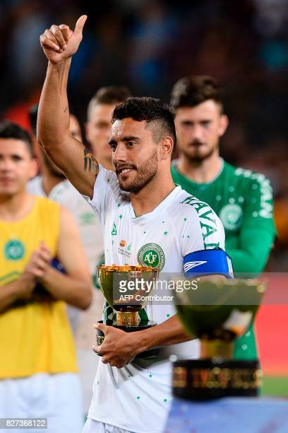 Chapecoense's defender Alan Ruschel gives a thumbs up to Barcelona players as he holds the second place trophy after the 52nd Joan Gamper Trophy...