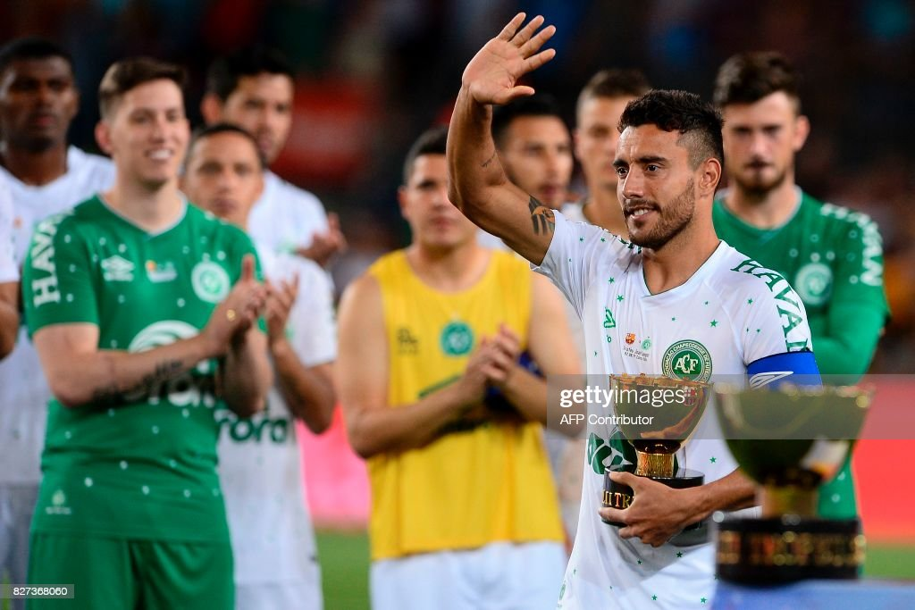 TOPSHOT - Chapecoense's defender Alan Ruschel waves to Barcelona players as he holds the second place trophy after the 52nd Joan Gamper Trophy friendly football match between Barcelona FC and Chapecoense at the Camp Nou stadium in Barcelona on August 7, 2017. Funds raised from the match will 'help Chapecoense rebuild institutionally and recover the competitive level it had before the tragedy', Barca said in a statement as the Brazilian side still reeling from a devastating plane crash that killed 19 players and 24 club officials last year. / AFP PHOTO / Josep LAGO