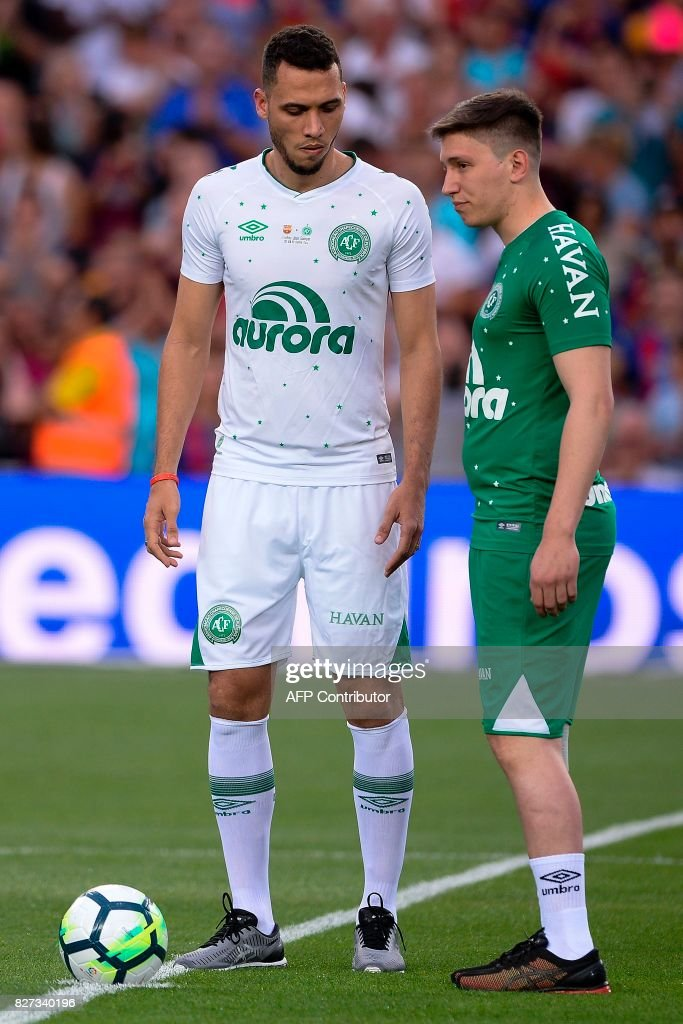 Chapecoense's defender Neto (L) and Chapecoense's former goalkeeper Jakson Follmann do the honour kickoff before the 52nd Joan Gamper Trophy friendly football match between Barcelona FC and Chapecoense at the Camp Nou stadium in Barcelona on August 7, 2017. Funds raised from the match will 'help Chapecoense rebuild institutionally and recover the competitive level it had before the tragedy', Barca said in a statement as the Brazilian side still reeling from a devastating plane crash that killed 19 players and 24 club officials last year. / AFP PHOTO / Josep LAGO