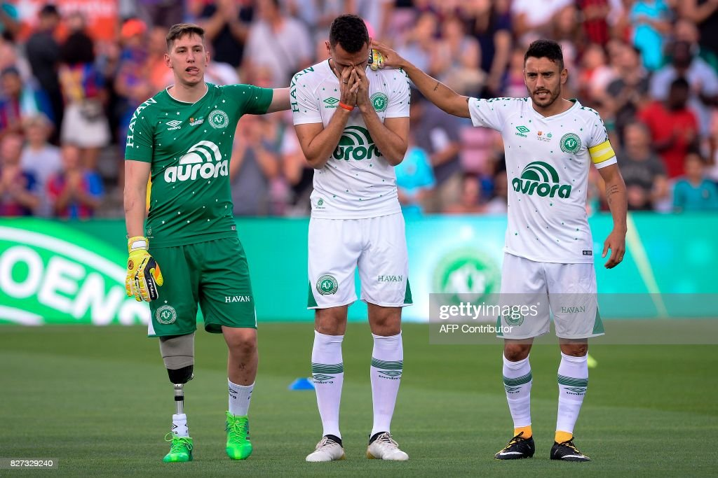 Chapecoense's defender Neto (C) cries between Chapecoense's goalkeeper Jakson Follmann (L) and Chapecoense's defender Alan Ruschel before the 52nd Joan Gamper Trophy friendly football match between Barcelona FC and Chapecoense at the Camp Nou stadium in Barcelona on August 7, 2017. Funds raised from the match will 'help Chapecoense rebuild institutionally and recover the competitive level it had before the tragedy', Barca said in a statement as the Brazilian side still reeling from a devastating plane crash that killed 19 players and 24 club officials last year. / AFP PHOTO / Josep LAGO