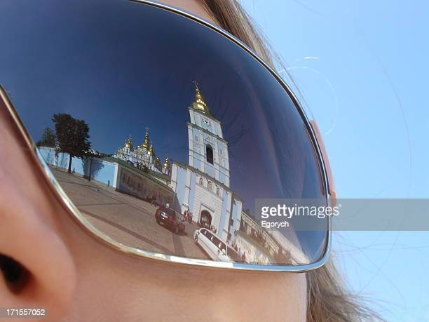 Chapel building reflected in a woman's sunglasses lens