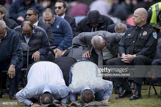Chapel Hill Police Chief Chris Blue listens as people pray during a service in a soccer field near the Islamic Association of Raleigh February 12...