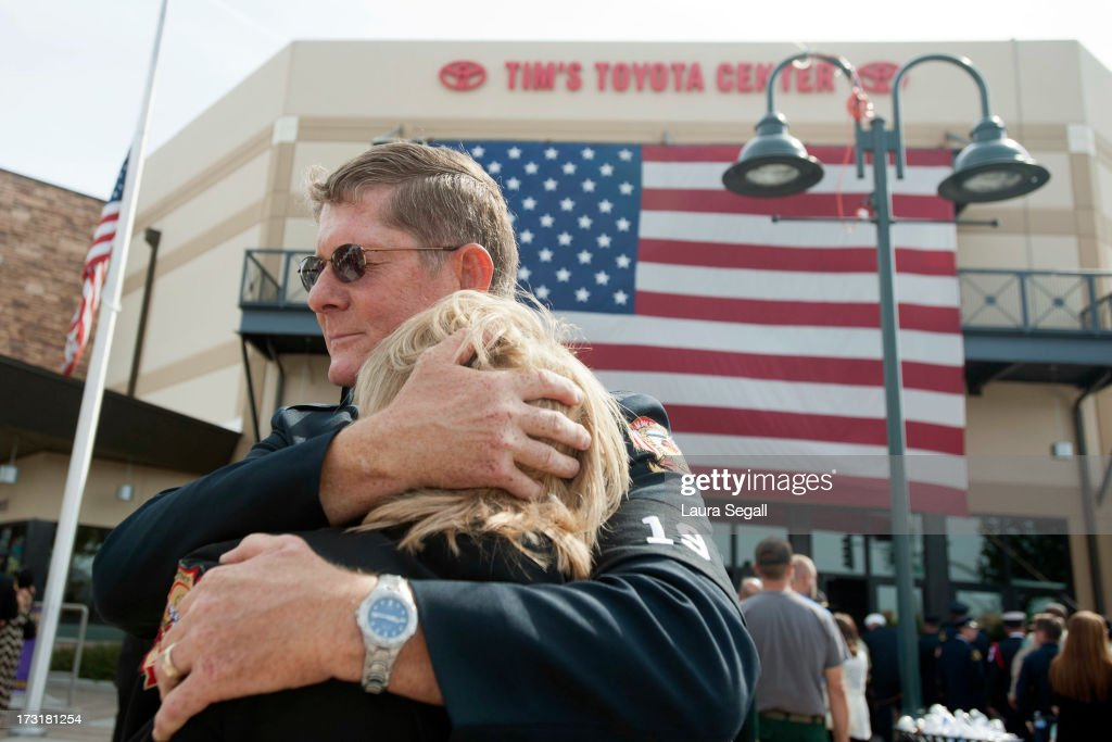 Chaplain Bob Ossler with the Mayer, Arizona fire department hugs Mary Dalton, assistant chief of the Sun City West Fire Department, at the entrance to a memorial service honoring the 19 firefighters killed in a wildfire at Tim's Toyota Center July 9, 2013 in Prescott Valley, Arizona. The firefighters, of the Granite Mountain Hotshots crew, died battling the fast-moving blaze on June 30.