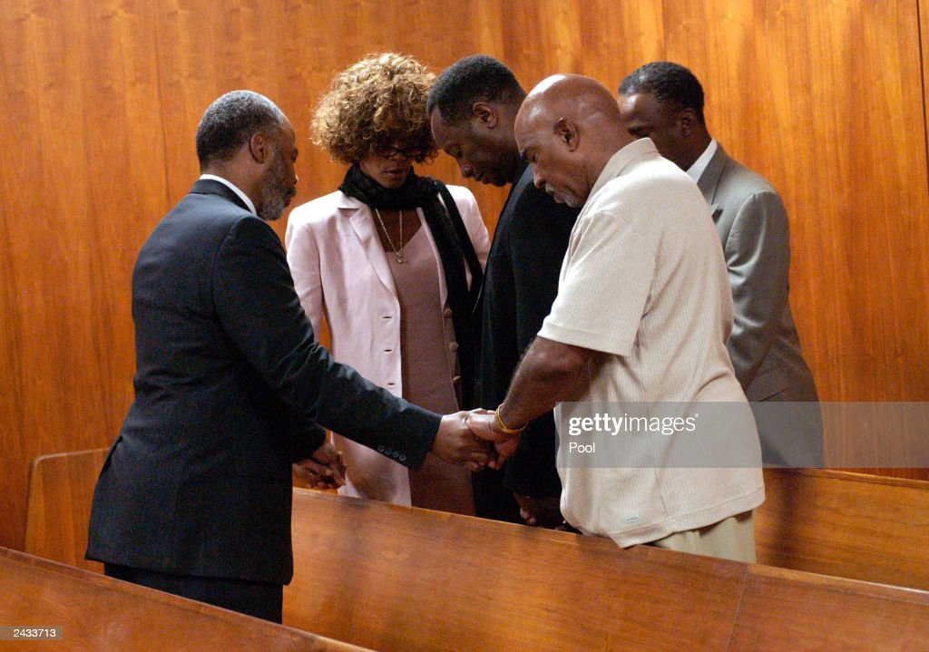 Chaplain Don Hughes (L) prays with Whitney Houston (2nd L) and the rest of her entourage after probation violation hearing for her husband, singer Bobby Brown at the DeKalb County Courthouse August 27, 2003 in Decatur, Georgia. Brown was sentenced to 14 days in the DeKalb County jail followed by 60 days of house arrest for violating conditions of his probation, stemming from 1996 DUI charges.