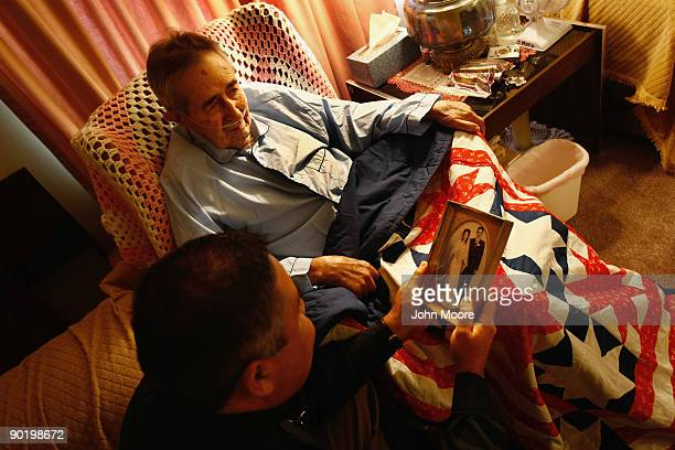 Chaplain Elias Burgos looks at a wedding photo of terminally ill patient Frank Martinez and his wife Dora during a home hospice visit to the...