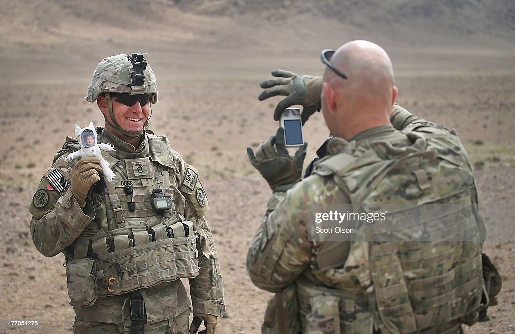 Chaplain (CPT) J. Joseph DuWors from Seattle, Washington with the U.S. Army's 4th squadron 2d Cavalry Regiment takes a picture of SSG Danny Doss from St. Louis, Missouri as he holds his 'Daric Doll' before the start of a live-fire exercise in the desert on March 6, 2014 near Kandahar, Afghanistan. The doll is a variation of a 'Daddy Doll' which soldiers give to their children to carry with them while the soldier is deployed in Afghanistan or Iraq. Doss has carried and photographed the doll in various locations in Afghanistan during his tour. President Obama recently ordered the Pentagon to begin contingency planning for a pullout from Afghanistan by the end of 2014 if Afghanistan President Hamid Karzai or his successor refuses to sign the Bilateral Security Agreement.
