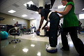 Chapman student Cindy Mack right makes sure stroke victim Janet Johnson keeps her balance as she does a carnival ring toss tossing a hula hoop over a...
